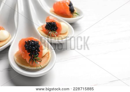 Tasty appetizers with black caviar and salmon in ceramic spoons on table