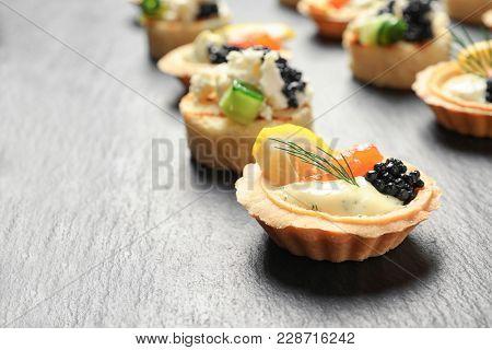 Tasty black caviar appetizers on slate plate
