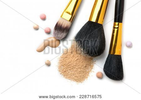 Cosmetic liquid foundation or cream, loose face powder, various brushes for apply makeup. Make up concealer smear and powder isolated on a white background. Products for Perfect face skin makeup