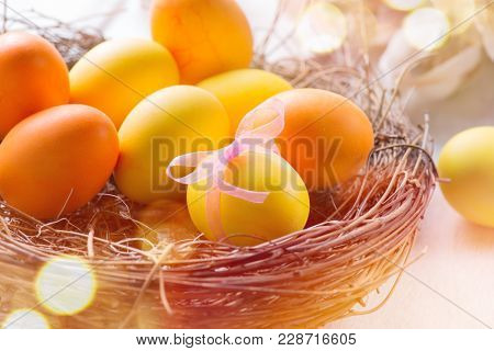 Easter colorful eggs in the nest. Beautiful colorful yellow and orange color eggs with decorations on white wooden table background, border design. Traditional Spring Holidays art design
