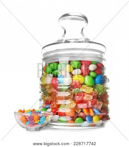 Glass jar with different colorful candies on white background