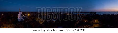 180 degree aerial night panorama of small town on the coast.