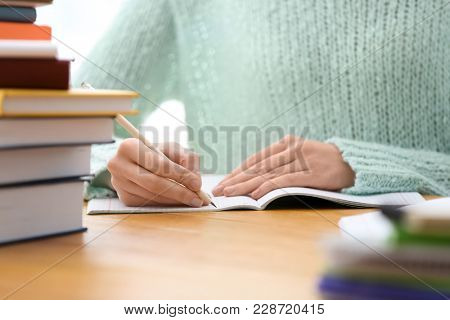Student preparing assignment at table, closeup. Studying process