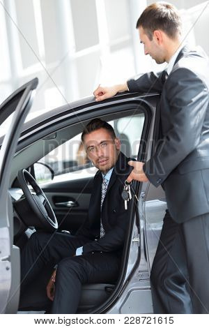 successful businessman, receiving the keys to the car from the seller in the showroom