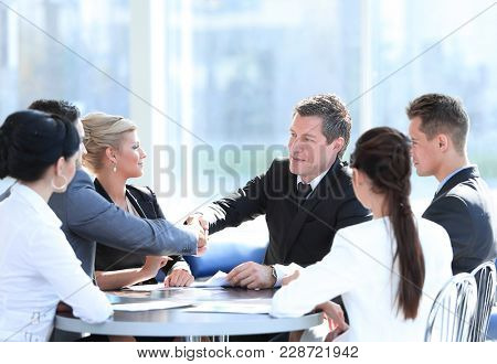 two business partners shaking hands on meeting