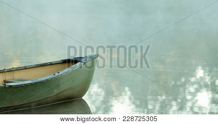 Canoe on glassy water with fog, negative space for text.
