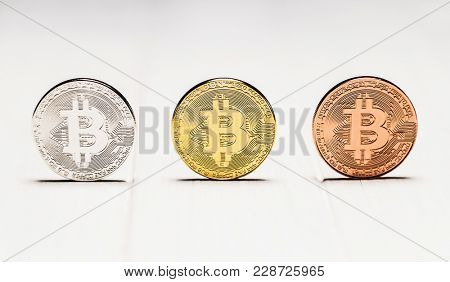 Set of three bitcoin coins on white background. Golden, silver and copper plated steel bitcoins. E-business, e-commerce concept