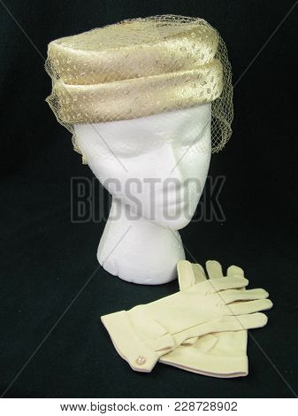 Gold Veiled Pillbox Hat And Gloves On A Woman Mannequin With A Dark Background