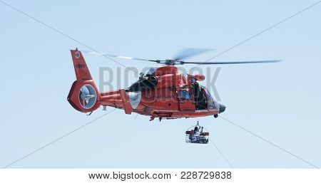 NORTH ATLANTIC OCEAN-DECEMBER 12, 2017: The United States Coast Guard lifts a paramedic from a ship during a medical evacuation in the North Atlantic Ocean north of Puerto Rico in December 2017.
