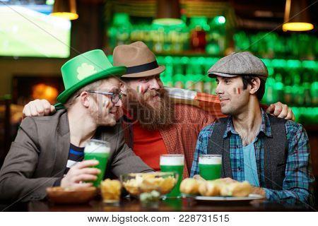 Three affectionate companions celebrating Saint Patrick day in irish pub