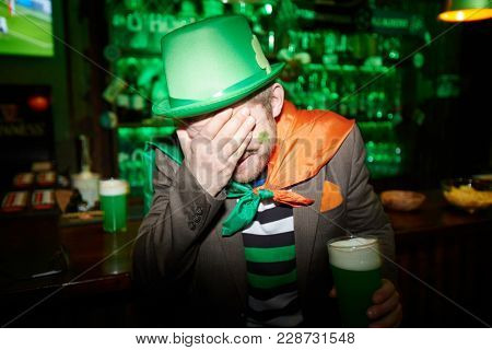 Shy irish man in green hat covering his face by hand with glass of beer in the other one