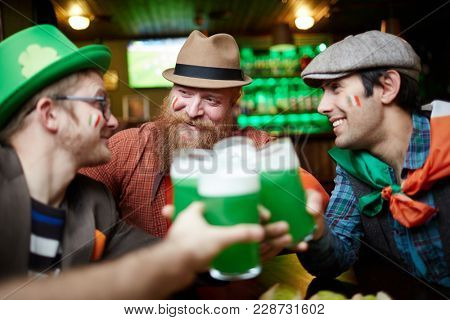 Happy young companions sitting in pub and toasting with green beer in glasses