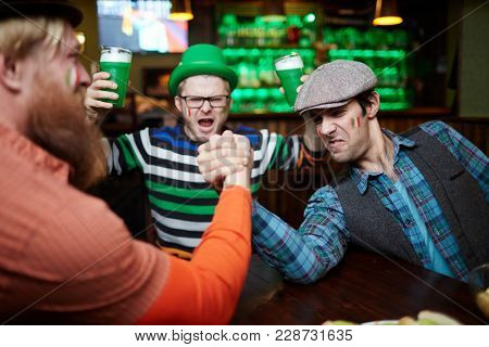 One of strong men winning his rival during armwrestling contest in pub