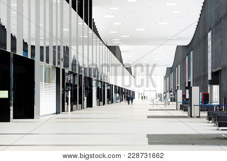 Long aisle in large contemporary airport with entrances to platforms and lounges