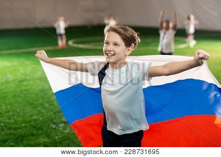 Happy youngster outstretching arms with national flag on football field