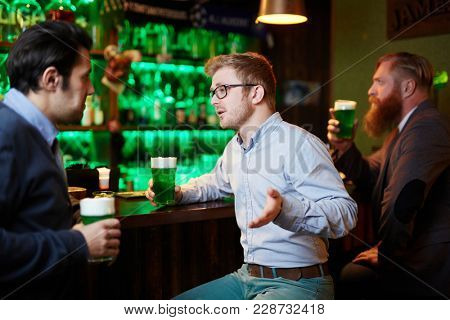 Friendly young man having talk while sitting by bar counter and drinking beer in pub