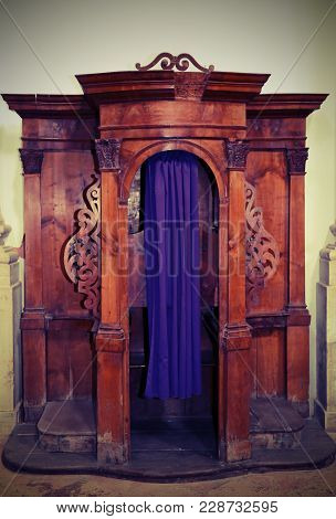 Ancient Wooden Confessional Inside A Church With Violet Curtain And Vintage Effect