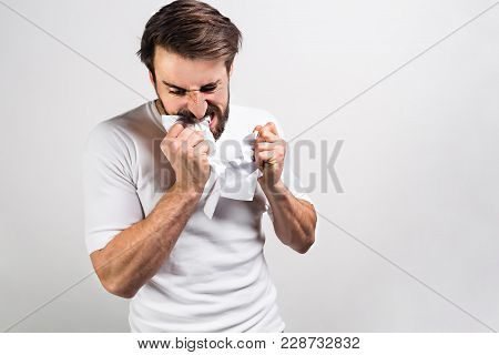 Angry And Mad Male Person In White Shirt Is Tearing Apart A Poor Paper. Isolated On White Background