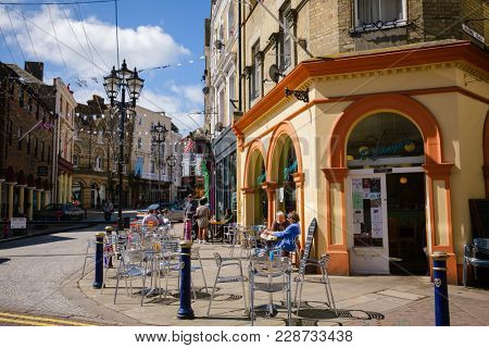 FOLKESTONE, UK - JUN 3, 2013: Customers dining at a sidewalk cafe on a sunny summer day