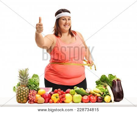 Overweight woman measuring her waist with a measuring tape and making a thumb up gesture behind a table with fruit and vegetables isolated on white background