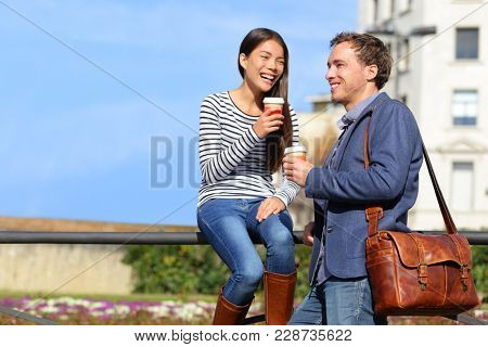 Friends talking drinking coffee on lunch break outdoor in the spring sun on city street. Happy Multiracial couple workers enjoying cafe date together outside. Young Asian woman, Caucasian man.