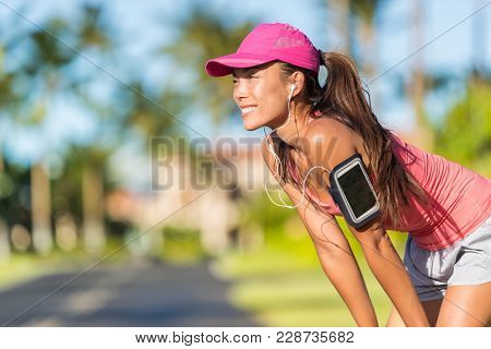 Happy summer running woman runner listening to music on phone sports armband with touchscreen and headphones earphones on city street, active lifestyle. Fitness Asian girl ready for jogging.