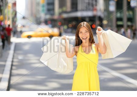 Shopping woman holding bags in New York City street with yellow taxi cab background. Beautiful happy summer shopper with bag walking outside smiling. Multiracial Asian Caucasian model, Manhattan, USA.