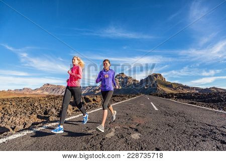 Girls runners running on road doing sprint hiit run cardio workout. Healthy active athletes jogging wearing sports activewear clothing in mountains nature.