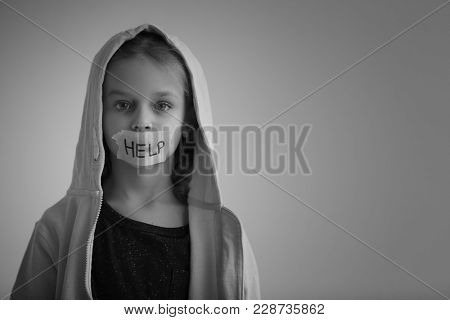 Sad little girl with taped mouth and word