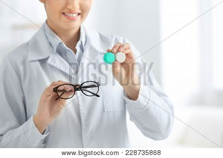 Female doctor holding contact lens case and glasses, closeup