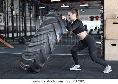 Young muscular woman flipping heavy tire in gym