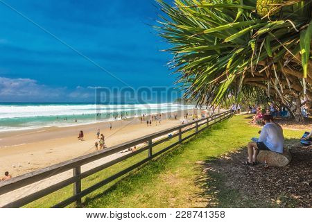 COOLUM, AUSTRALIA, FEB 18 2018: People enjoying summer at Coolum main beach - a famous tourist destination in Queensland, Australia.