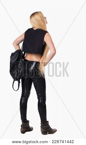 back view of standing young beautiful  woman.  girl  watching. Rear view people collection.  backside view of person.  Blonde in leather pants standing with a backpack standing with hands on hips.
