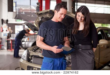 A man mechanic and woman customer discussing repairs done to her vehicle