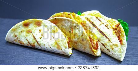 Tacos. Mexican tortillas with a filling of hot meat. Close-up of tacos. Mexican tacos with beef.