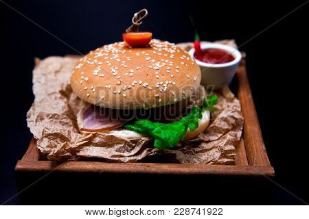 A juicy burger. Burger with marble beef, fork with knife and chili sauce on the newspaper