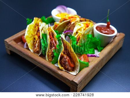 Tacos and chili sauce. Mexican tortillas with a filling of hot meat. Close-up of tacos.