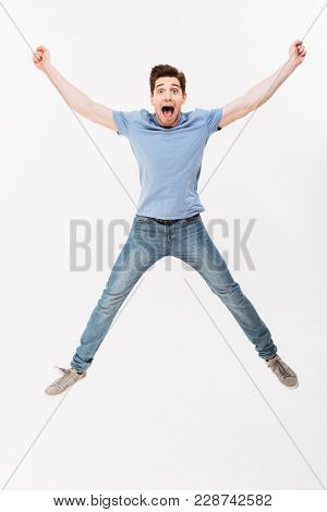 Full-length photo of joyous man 30s in casual t-shirt and jeans jumping and throwing up arms in air isolated over white background