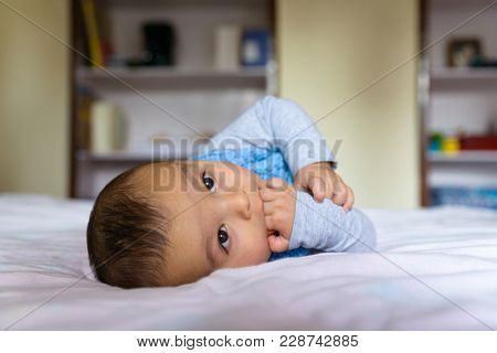 Eurasian baby lying on bed