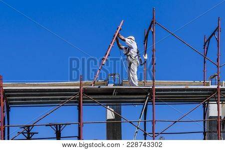 Builder Worker In Safety Protective Equipment Installing Scaffolding Construction Site
