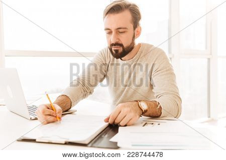 Image of smart adult man 30s in casual clothing writing notes on paper document while working in home office