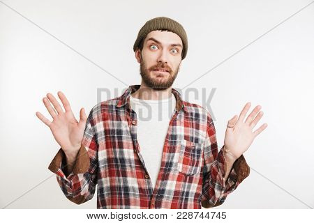 Portrait of a shocked bearded man in plaid shirt looking at camera isolated over white background