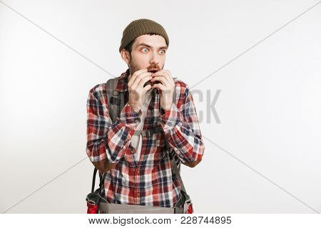 Portrait of a scared bearded man in plaid shirt carrying backpack and looking away isolated over white background