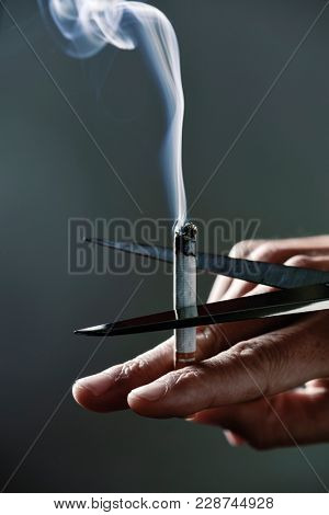 closeup of a young caucasian man cutting a lit cigarette with scissors, depictign the idea of quitting smoking