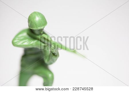 Macro closeup of little green army men toys - Military soldier firing a machine gun - focus on face