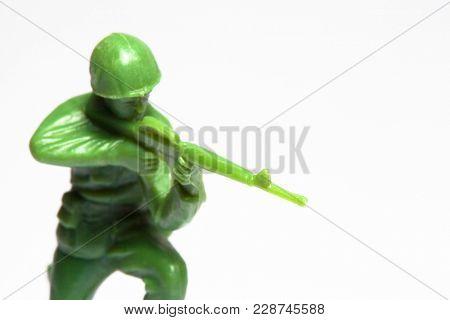 Macro closeup of little green army men toys - Military soldier firing a machine gun - focus on gun