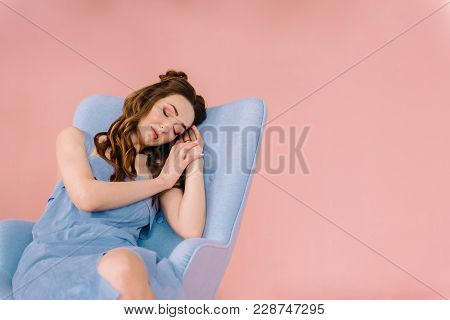 A Girl With Long Flowing Hair And A Blue Dress, Fell Asleep On A Blue Armchair In A Pink Room