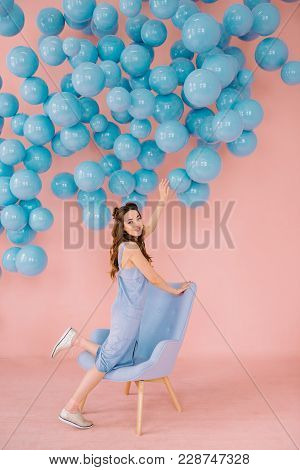 A Girl Of Small Stature In A Pink Room Is Playing With Blue Balls