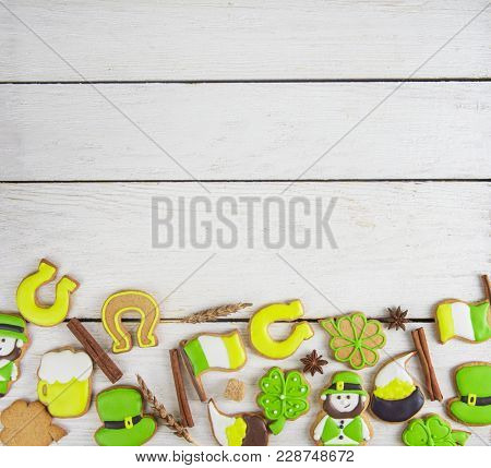 Gingerbreads cookies for Patrick's day on white wooden background