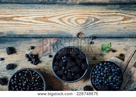 Blueberry, Blackberry, Blackcurrant In Bowls On A Wooden Background